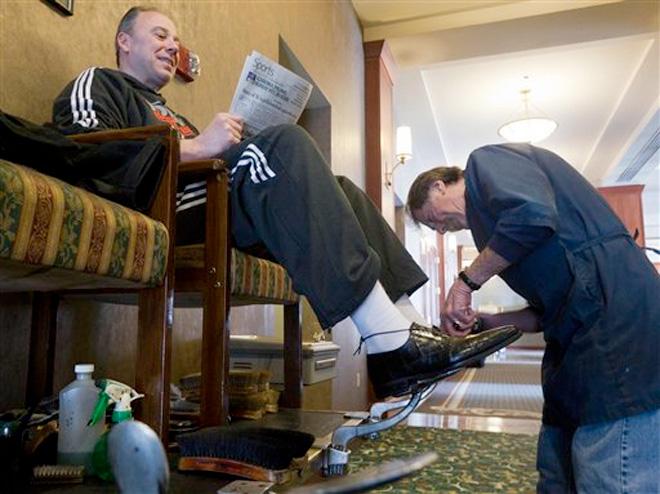 Jim Walker, 72, works on the shoes of Idaho Stampede Assistant Coach Barry Rohrssen, Thursday Jan. 17, 2013. (AP Photo/Idaho Statesman, Darin Oswald)