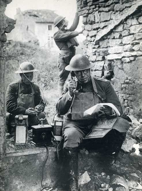 An American Signal Corps officer tests a German army phone left behind as the Germans retreated in Oct 1918 (Illustrated Hist of US)