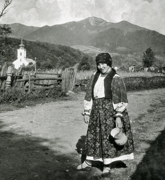 """A Living Lens"": A Jewish woman in a Carpathian mountain town posing on a country road, water pitcher in hand"